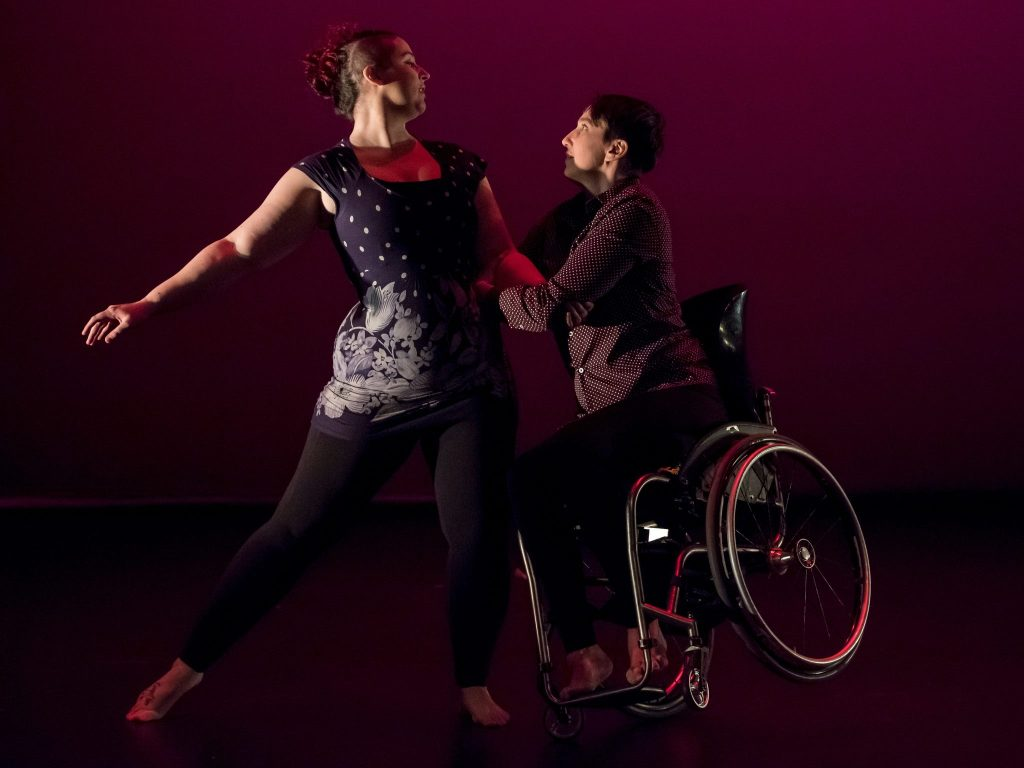 Masculine presenting wheelchair user dances with femme presenting ambulatory dancer.