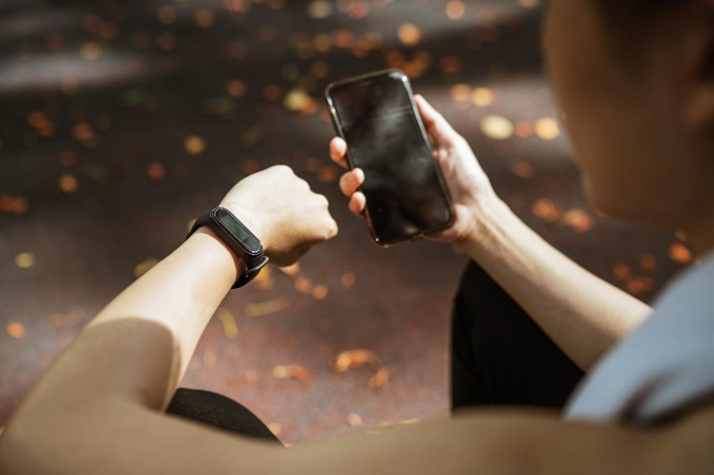 A woman holds a phone and looks at digital self-tracking device on wrist.
